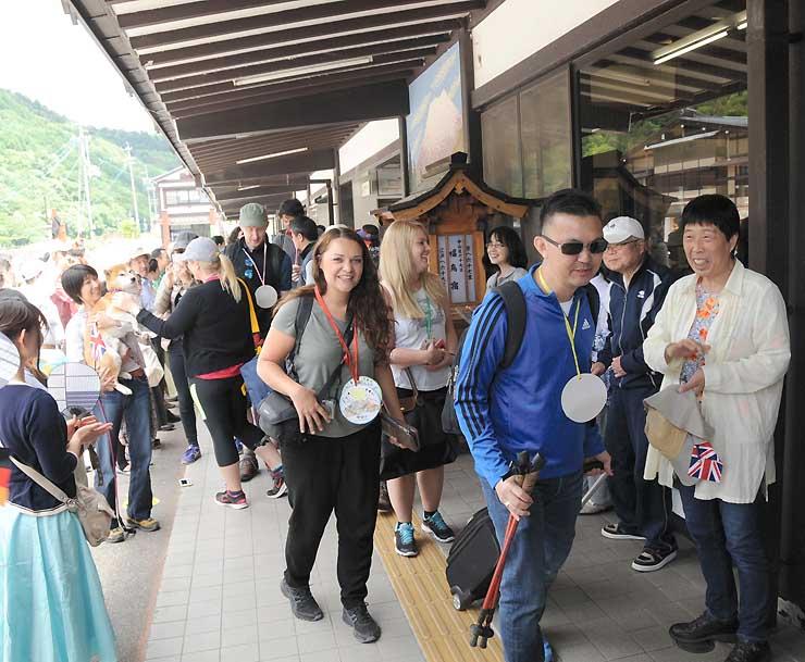 木曽福島駅前で、出迎えた住民の間を歩く海外の旅行代理店の一行