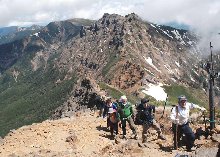列になって赤岳山頂を目指す登山者たち。後方に八ケ岳の峰々が連なる