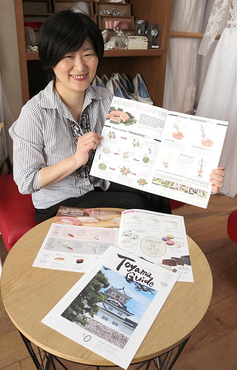 外国人向け観光情報誌「Toyama Guide」を手にする田島さん