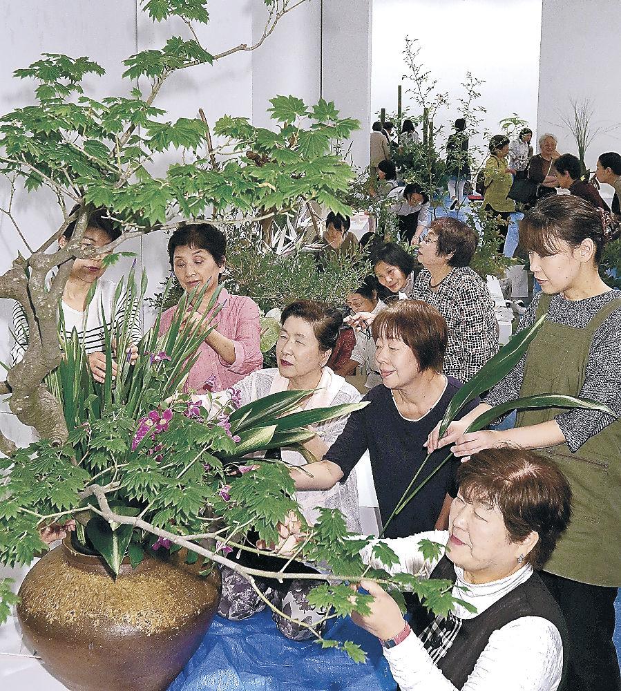 選び抜いた花材で生命力あふれる作品を仕上げる華道家=金沢21世紀美術館
