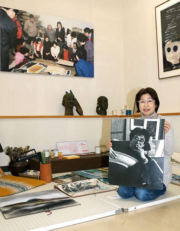 高橋信一の写真を手に、アトリエを再現したコーナーを紹介する長女の須田芳子さん=6日、佐渡市相川米屋町