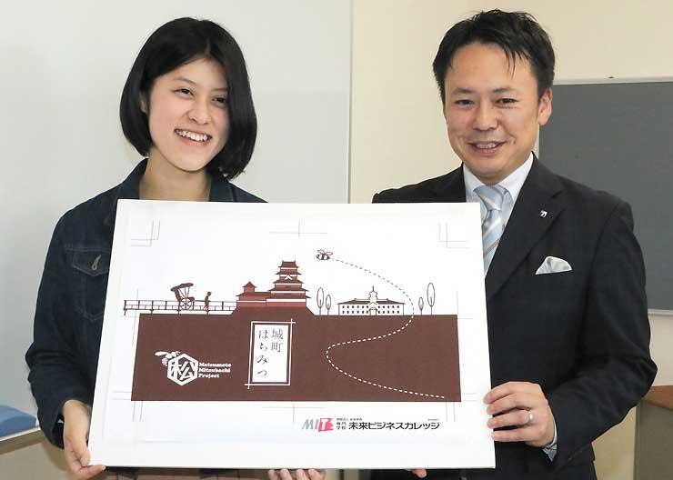 完成したラベルデザインを披露する中幡さん(左)