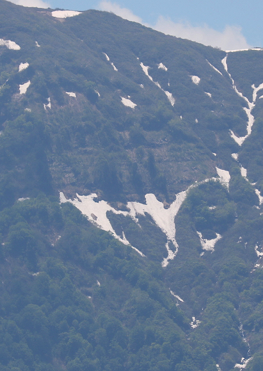 人形山の山肌に現れた「ひとかた」。中央の残雪の部分が手をつないだ姉妹のように見える=南砺市小来栖から