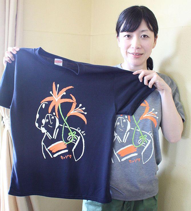 トビシマカンゾウが描かれたTシャツを手にする市地域おこし協力隊の西本佐和子さん=佐渡市願