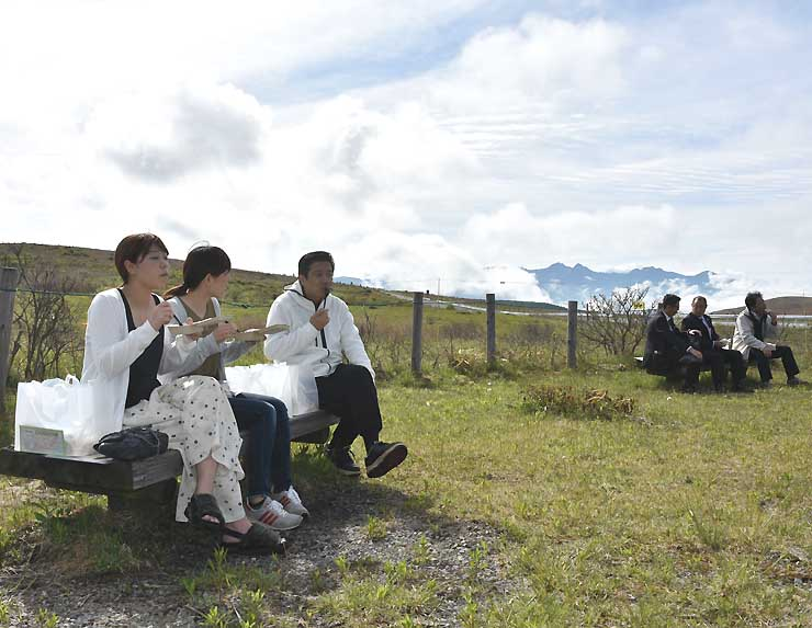 屋外のベンチで霧ケ峰の眺めを楽しみながら朝食を取るツアーの参加者たち