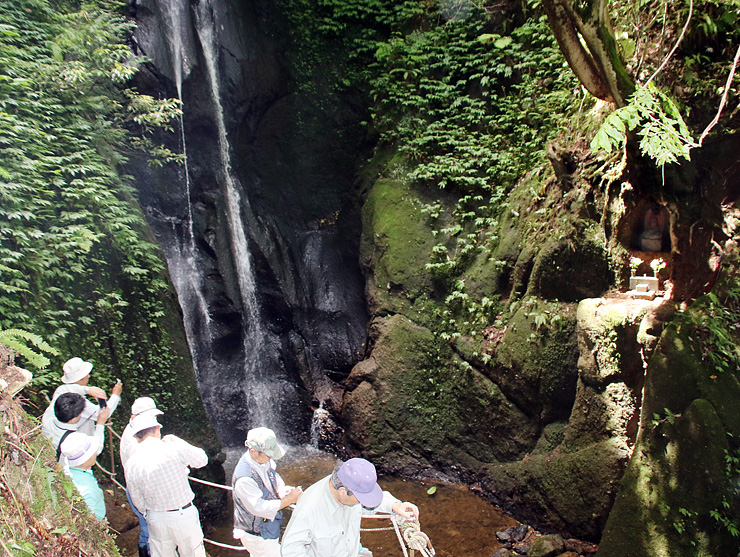 整備された遊歩道から滝や不動尊(右)を眺める参加者