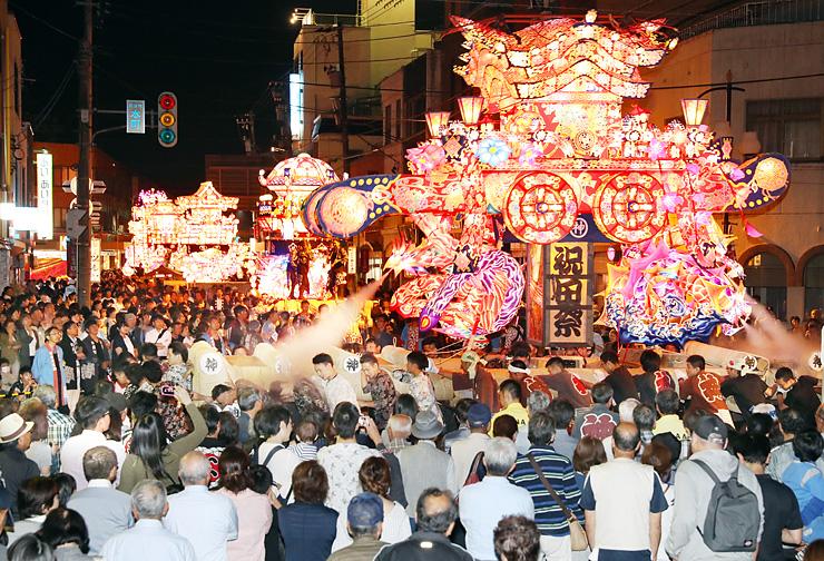 大勢の見物人の前で威勢よく練り回される夜高行燈=砺波市本町