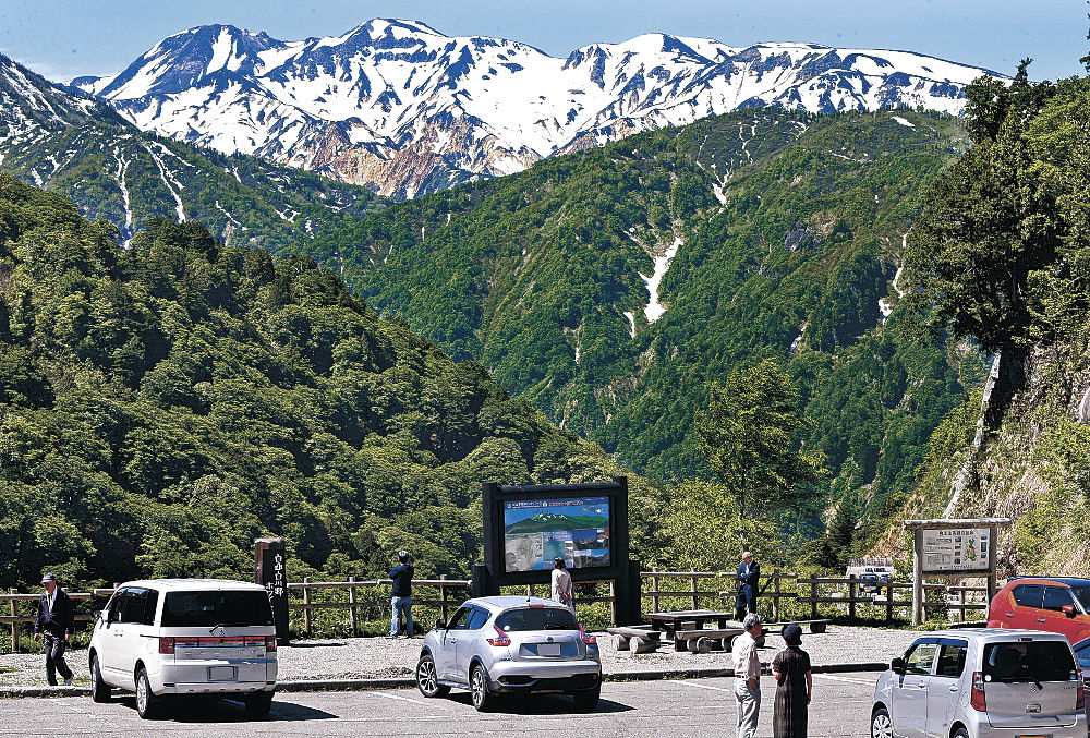 雪の残る白山や木々の緑が織り成す風景を楽しむ観光客=白山市の白山白川郷ホワイトロード