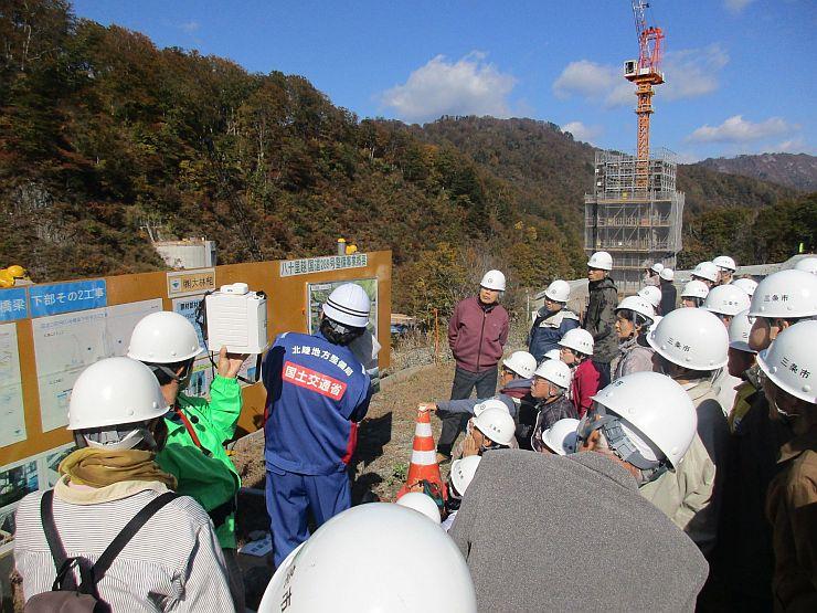 橋の工事現場を見学するバスツアー参加者ら=2016年10月、三条市(三条市提供写真)