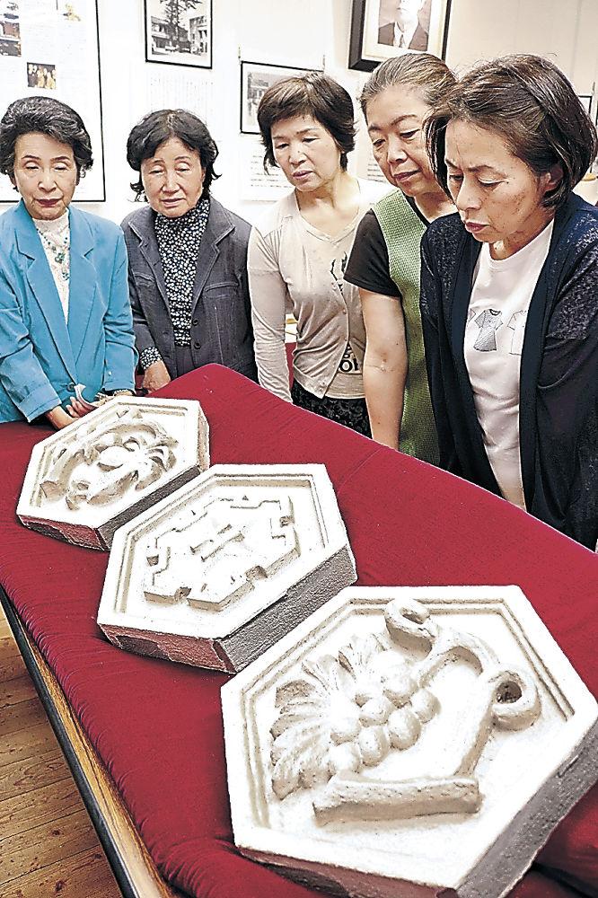 移設された校章と装飾を眺める同窓会員=金沢市の北陸学院ウィン館