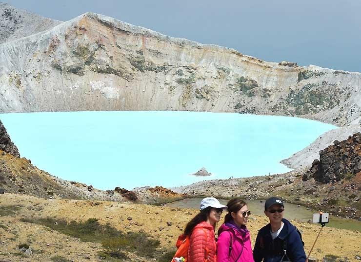 美しい水色に輝く湯釜。記念写真を撮る外国人観光客も目立った=15日