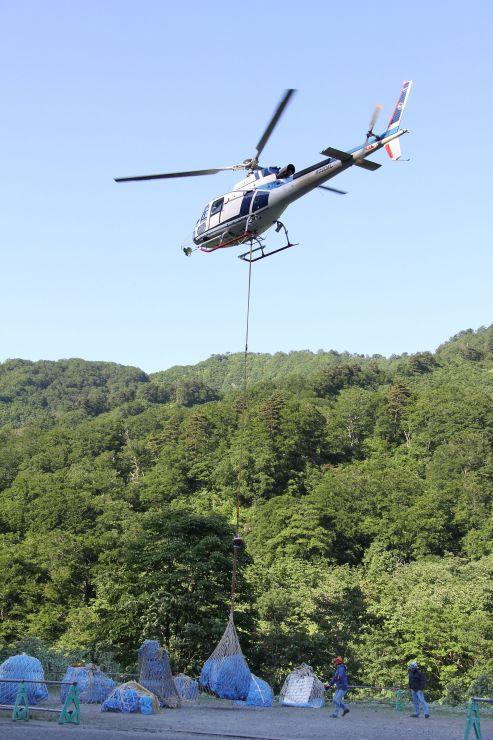 山小屋に荷物を運ぶヘリコプター=15日、胎内市下荒沢