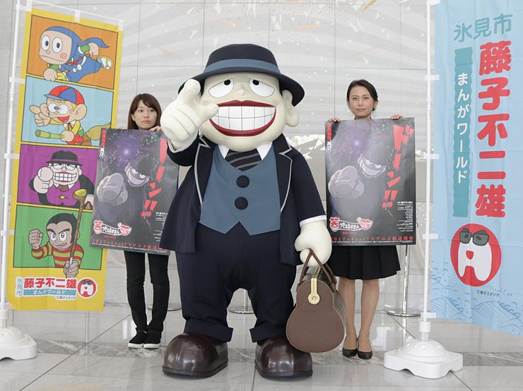 氷見市潮風ギャラリーで開かれるキャラクターグリーティングをPRする喪黒福造(中央)=北日本新聞社