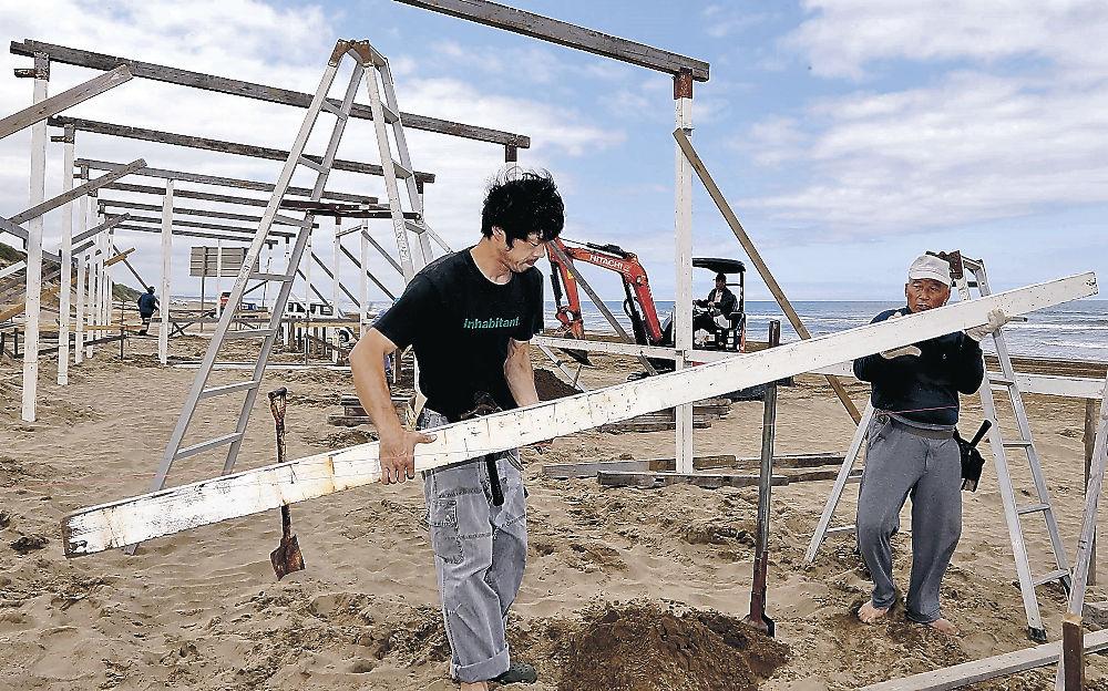 浜茶屋の組み立てを進める関係者=羽咋市の千里浜海岸