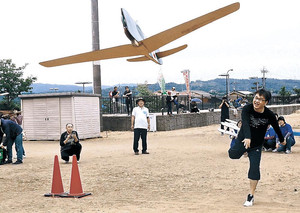 ジャンボ紙ひこうきを飛ばす参加者=かほく市の県立看護大