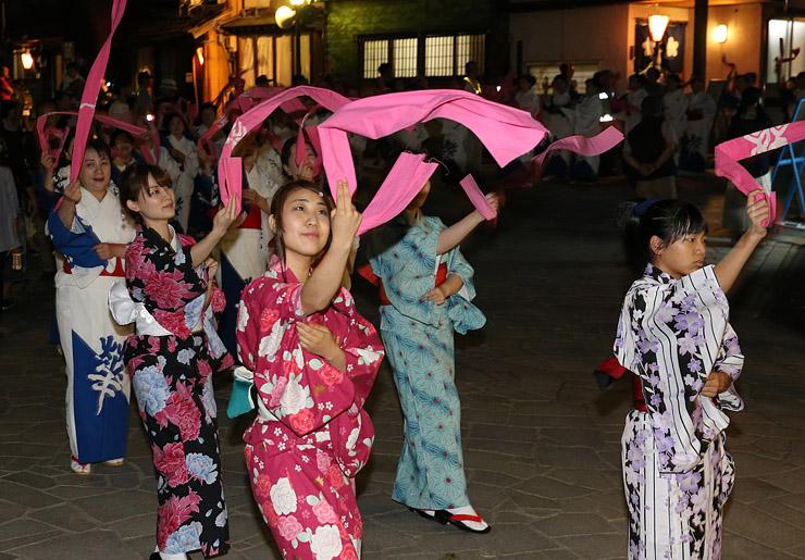 手ぬぐいを手に「エンヤシャ ヤッシャイ」の掛け声に合わせて踊る女性たち=高岡市金屋町