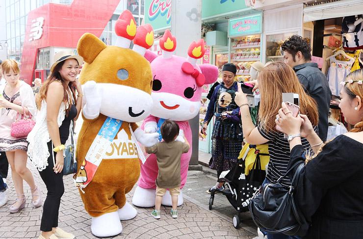 買い物客や観光客と記念撮影するメルギューくん(中央左)とメルモモちゃん(同右)=東京・原宿