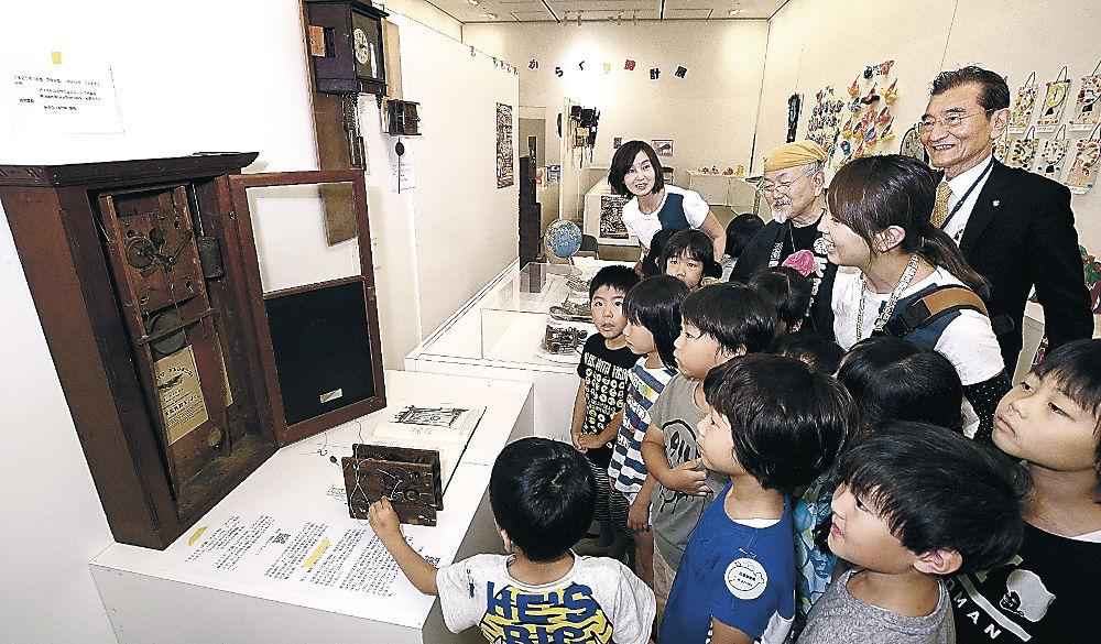 復元された古い時計に見入る来場者=金沢21世紀美術館