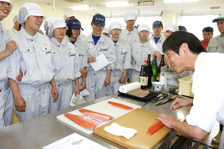 藤田さん(右)にますずしの調理法を教わる生徒たち