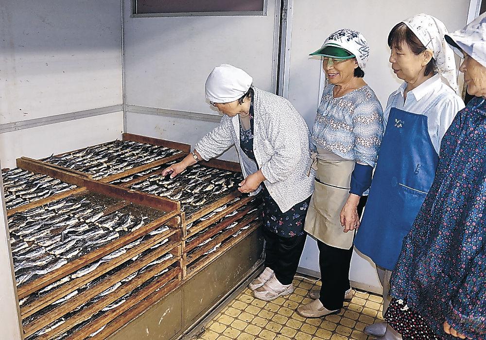 焼き上がったトビウオを乾燥させるメンバー=珠洲市三崎町小泊