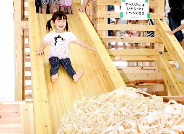 かんなくずに向かって勢いよく滑り台を滑る子ども=24日、福井市の県産業会館