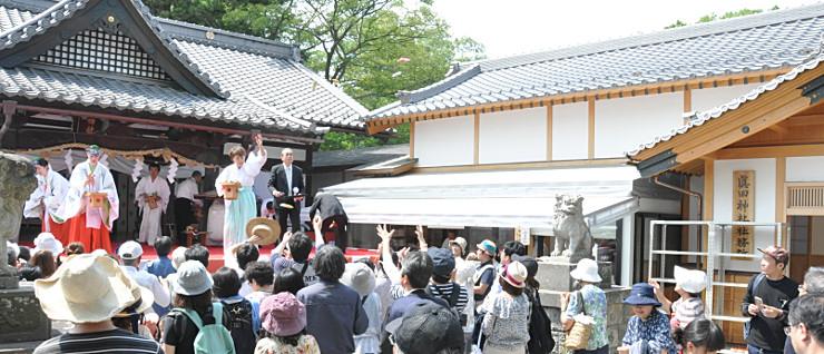 上田城跡公園内の真田神社。社務所(右)の新築を祝ってお菓子を振る舞い、多くの人が受け取った