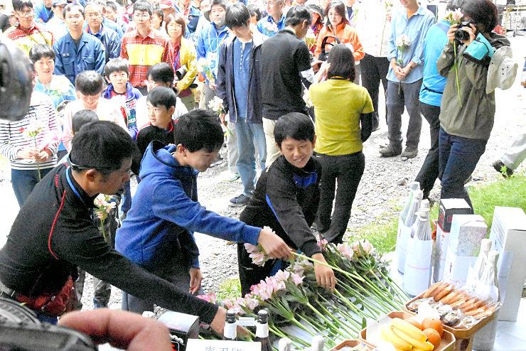 竹沢長衛の碑の前で花を手向ける参加者たち
