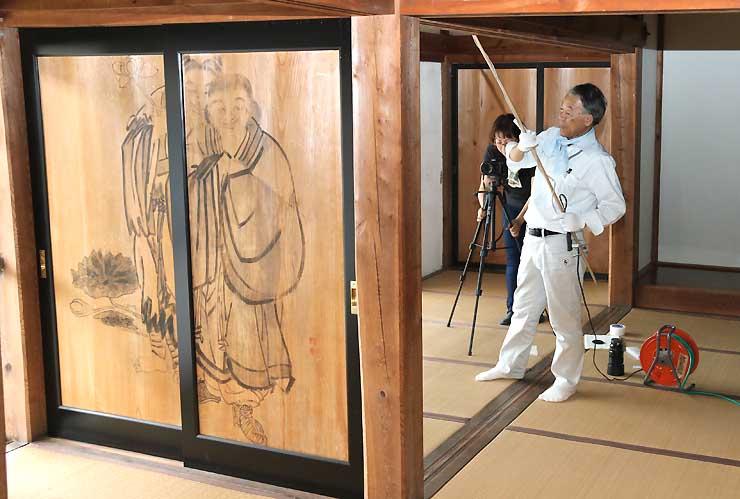 戸板に描かれた絵を撮影する原さん(手前)ら=27日、伊那市高遠町の樹林寺