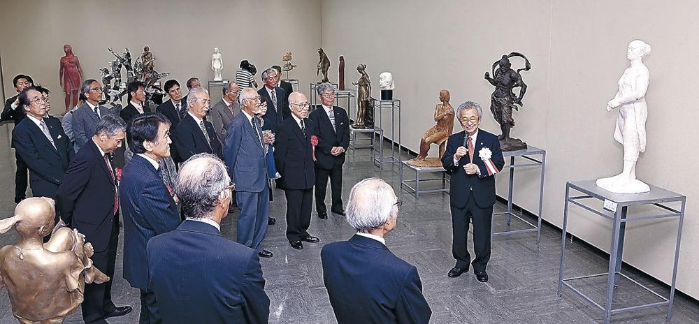神戸理事長(右)から作品解説を聴く開会式出席者=金沢市の石川県立美術館