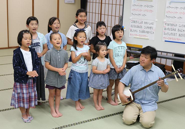 平野理事(右)の指導で元気よく歌う子どもたち