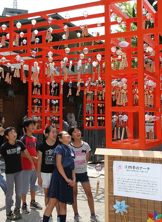 境内に飾られた風鈴を眺める白山小の児童=29日、新潟市中央区の白山神社