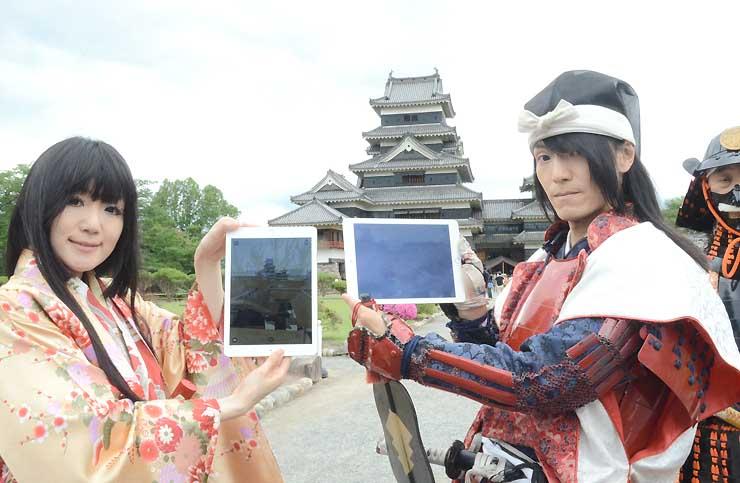 江戸時代の松本城を再現した景色が見られる端末を手にする「国宝松本城おもてなし隊」のメンバー=30日、松本市