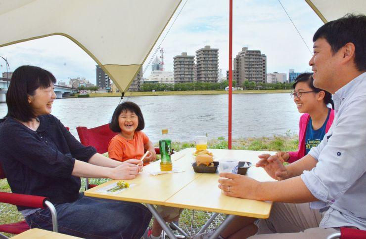 家族連れらが川辺で飲食を楽しんだ「ミズベリング信濃川やすらぎ堤」=1日、新潟市中央区