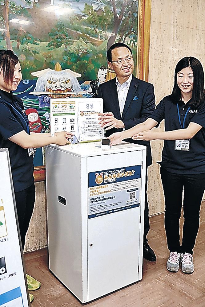 専用ボックスに小型家電を投入する山野市長(中央)=金沢市役所