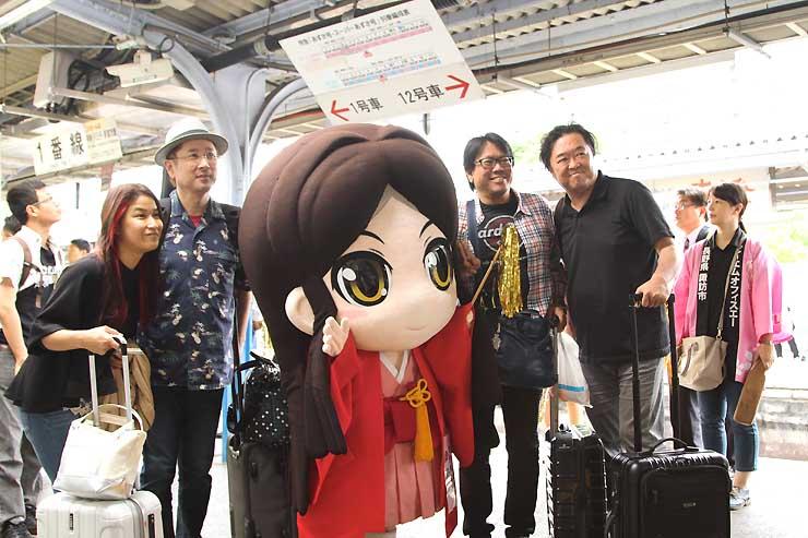 JR上諏訪駅に着き、諏訪市公認キャラクター「諏訪姫」の着ぐるみと記念撮影する観光客