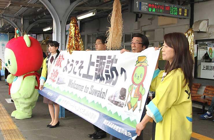 上諏訪駅構内で「ようこそ上諏訪へ」の横断幕を掲げて乗客を出迎える観光関係者