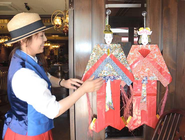 カフェの店先に七夕人形を飾る店員