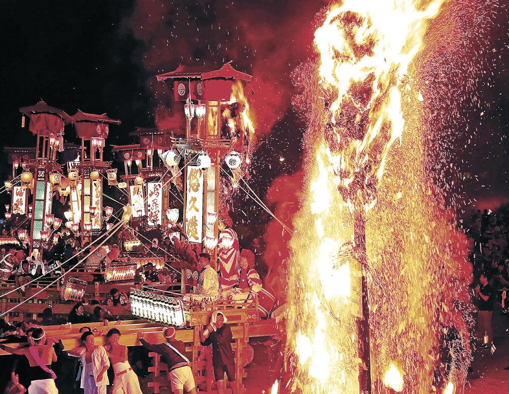 燃えさかる大たいまつのそばを乱舞するキリコ=7日午後9時45分、能登町の宇出津港いやさか広場
