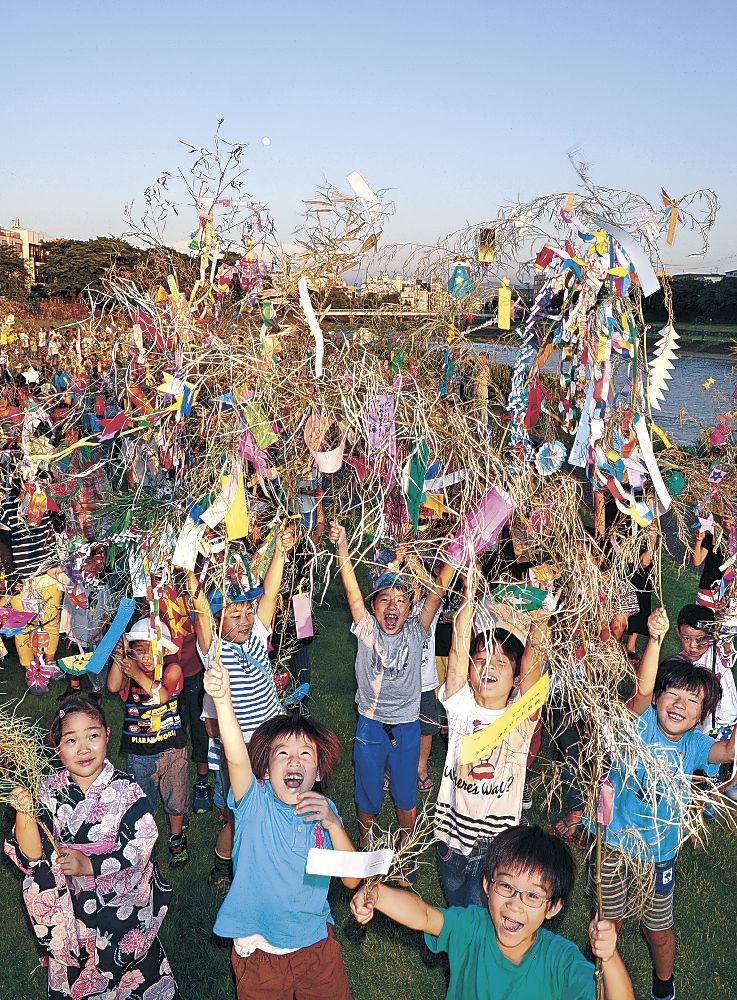 七夕飾りを持ち寄った参加者=金沢市中央通町の犀川河川敷