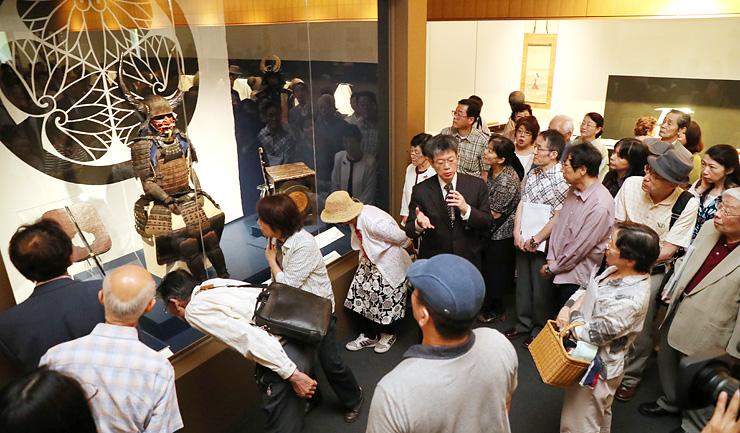 鈴木副主幹(中央)の解説を聞きながら、家康の甲冑に見入る来場者=県水墨美術館