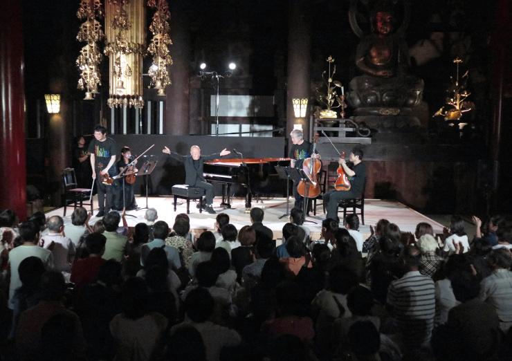 荘厳な善光寺本堂内で、久石譲さん(中央)のピアノと室内楽の奉納コンサートに大勢が聴き入った