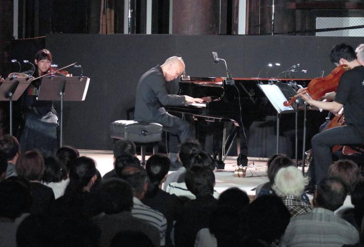 善光寺本堂での奉納コンサートでピアノを弾く久石譲さん(中央)