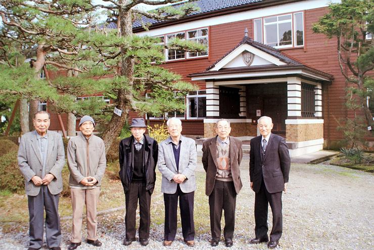 田中小学校の旧本館を訪れ、前庭で記念撮影する卒業生