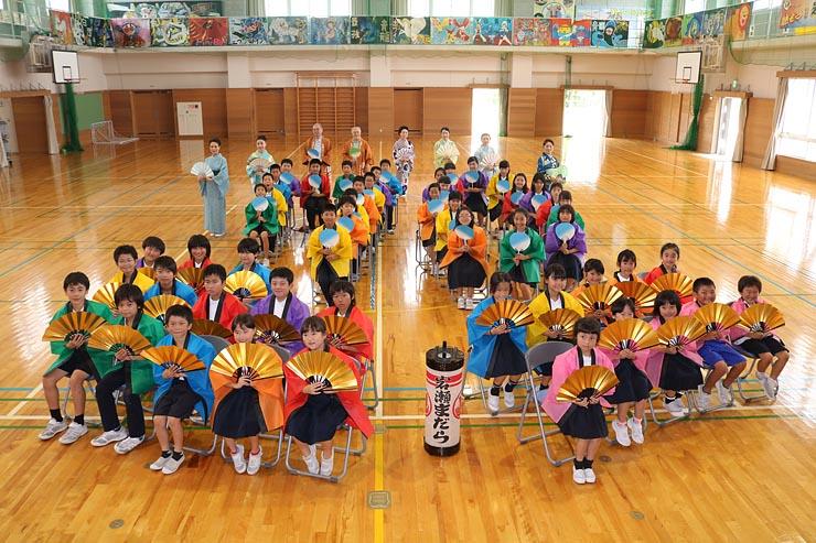 寄贈された法被を着て扇子やうちわを手にする児童ら