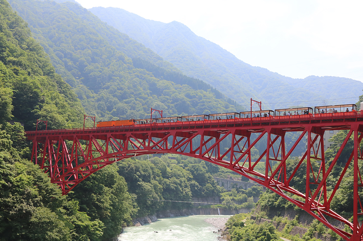 宇奈月-笹平間で10日ぶりに運転が再開され、新山彦橋を渡るトロッコ電車=黒部市黒部峡谷口