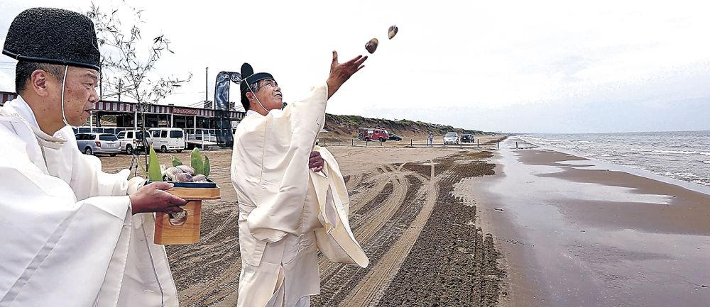 夏のにぎわいと安全を願ってハマグリを海に投げ入れる神職=羽咋市の千里浜海水浴場
