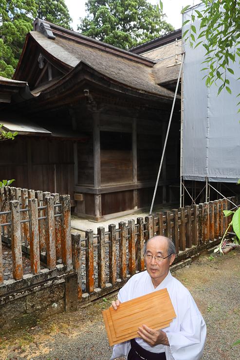 12年ぶりに屋根のふき替えが行われる埴生護国八幡宮。屋根にふくサワラの板を手にする埴生宮司=小矢部市埴生