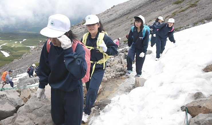 雪が残る道を山頂目指して登る生徒たち=11日、乗鞍岳