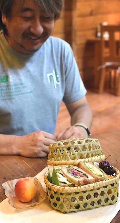 戸隠伝統の竹細工の弁当箱にサンドイッチなどを詰めた特製の弁当を披露する秦さん
