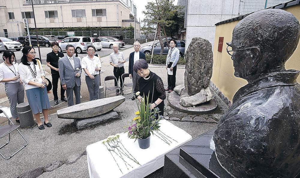 顕彰碑前に花を供える関係者=金沢市本多町3丁目